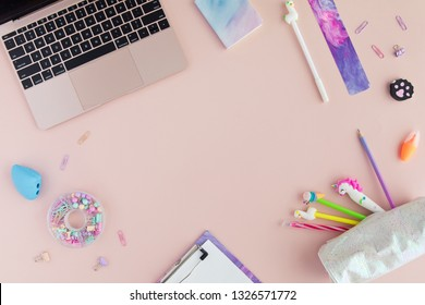 Flat lay of kawaii stylish school stationery and laptop on pink background. Back to school concept. Top view of pastel office desk