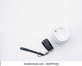Flat lay of key car and coffee cup on white background, travel concept with copy space