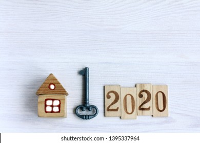 Flat lay with key, home and wooden numbers on the wooden table,