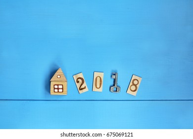 Flat lay with key, home and wooden numbers on the blue table, top view / Detached house in 2018