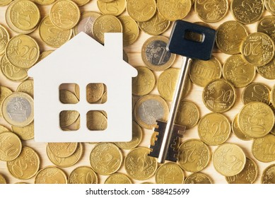 Flat lay of key and toy house over Euro coins