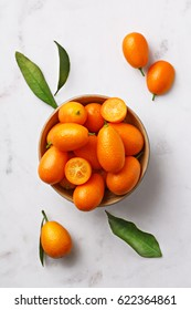 Flat lay kumquats in a bowl on a marble background. Top view