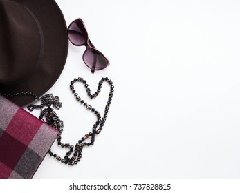 Flat lay with lady's clutch, hat, sun glasses, necklace. Autumn colours accessories on white background