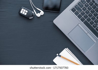 Flat lay of laptop computer notebook, smarthphone, earphone, pencel and car key with copy space for text