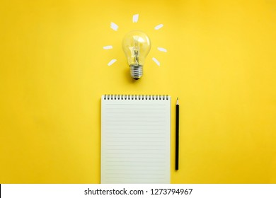 Flat lay of light bulb and empty memo pad and pencil on yellow background with texts. Conceptual brain storming still life.