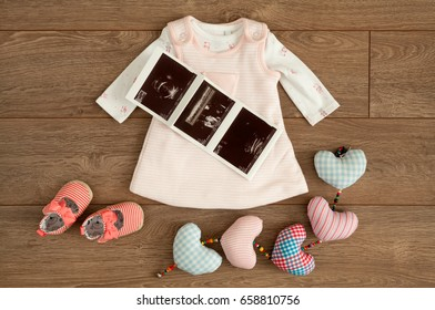 Flat lay of little pink dress and tiny shoes of infant baby girl along with sonography pictures sonograms and colorful cotton hearts on brown wooden surface with copy space.
