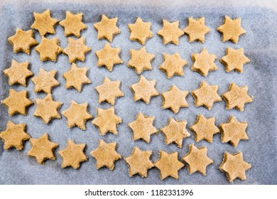 Flat lay - looking down on baking paper sheet with messy star shaped Christmas cookies  - dough is ready to bake