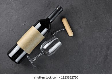Flat lay of lying red wine bottle with empty label, corkscrew and glass for tasting on dark gray concrete background