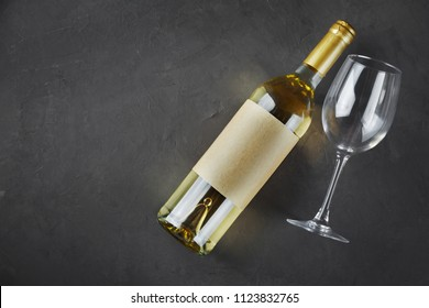 Flat lay of lying white wine bottle with empty label and glass for tasting on dark gray concrete background
