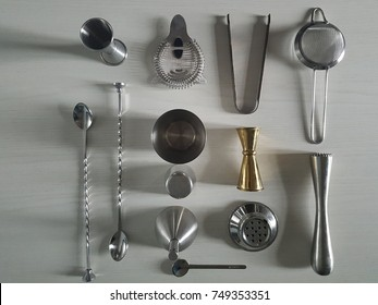 Flat lay made with bartender tools such as jiggers, shakers, mixing spoons and strainers, all resting on a white wooden table top