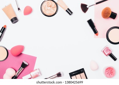 Flat lay makeup background frame of professional cosmetic products and accessories on white table, top view.