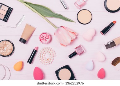 Flat lay makeup and feminine accessories on pink background. Pattern background of beauty products on wooden table, top view.