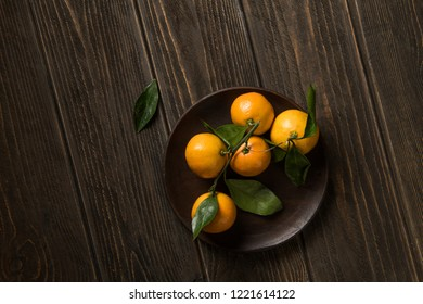 Flat lay of mandarins with leaves on dark wooden background
