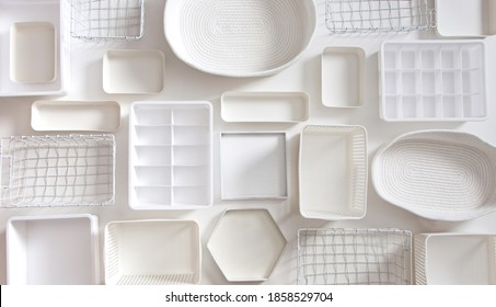 Flat lay of Marie Kondo's white storage boxes, containers and baskets with different sizes and shapes for tidying up wardrobe. KonMari method organizer boxes set. Closet organizing concept.