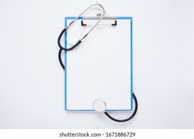 Flat lay medical stethoscope composition with clipboard and blank paper tempelate