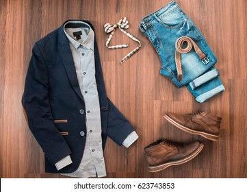 Flat lay of mens casual clothes set such as blue suit with patches, jeans, checkered bowtie, belt and shoes on brown wooden background. Top view.