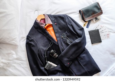 Flat lay of mens suit and travel essentials on white bed