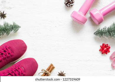 Flat lay of Merry Christmas and Happy new year for healthy and active lifestyle concepts. Composition with dumbbells, sport shoes and Christmast decoration on grunge white wood background.