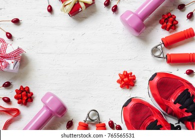 Flat lay of Merry Christmas and Happy new year and any holidy present boxes for healthy and active lifestyle concepts. Composition with dumbbells, sport shoes and red gift boxes with bow on wood