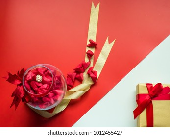 flat lay minimal concept for valentine's day and chinese new year event with heart (origami)in beauty jar with gold ribbon and gift box on red background