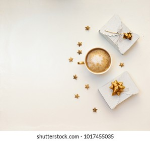 Flat lay  minimal desk with cup of coffee and gift box