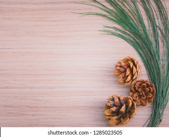flat lay and minimal object and idea decoration for new year and christmas concept from brown pine corn and green pine leaf arrange on wooden texture background