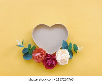 Flat lay of minimal workspace blank heart shaped box with colorful roses on yellow background, spring and summer concept.