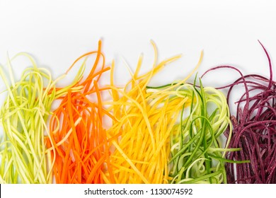 flat lay of mix red, yellow, orange carrots and cucumber finely julienned vegetables for salad, concept healthy eating with copy space