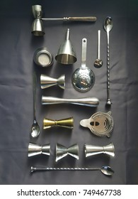 Flat lay of mixologist tools made of shiny metal, resting on a dark grey cloth