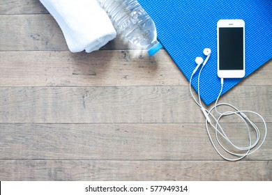 Flat lay of mobile phone with earphone and yoga mat, towel and bottle of water on wood floor, Copy space