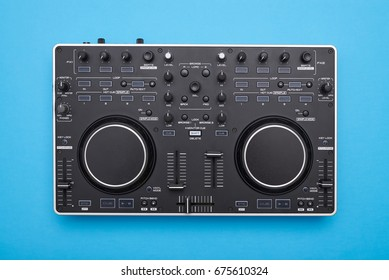 Flat lay of modern DJ mixer on blue background
