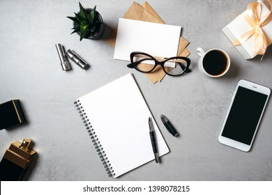 Flat lay modern minimal home workspace desk with blank notepad, glasses, smartphone, succulent plant, kraft envelope, paper card, coffee cup.  Top view feminine desk business lady blog hero.