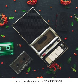 Flat lay music audio cassette and player, nostalgic image top view of retro technology from 80s and 90s with wild berry fruit decoration arrangement