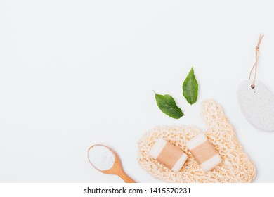 Flat lay natural cosmetics and accessories for skin cleansing and exfoliation, sponge, soap, pumice stone and spoon of clay powder. Basic hygiene and body care items on white background, copy space.
