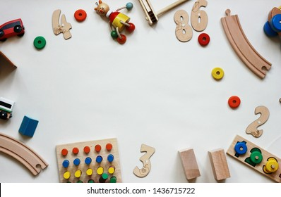 flat lay with natural toys for the development of children after school, numbers letters cubes and puzzles and puzzles on the table, cars and other materials from wood on a white background,