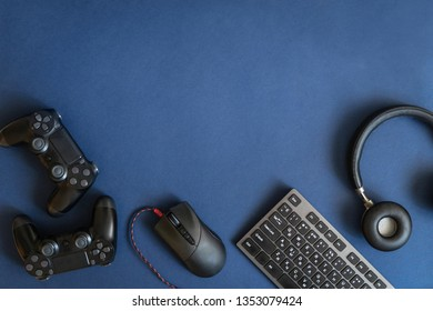 Flat lay of new modern button joystick, keyboard, headset and computer mouse lying isolated against dark blue background with place for advertised text