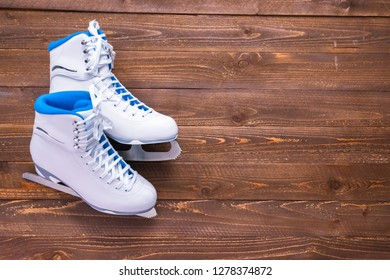 Flat lay. New white figure skates on a wooden boards.