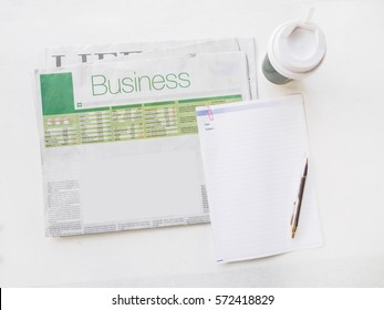 Flat lay newspaper and empty space with blank note and coffee cup on white desk workplace