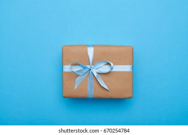 Flat lay of nice box wrapped and decorated with bow on blue background with copy space