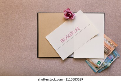 Flat lay of a notebook blogger life  with money inside pages in a golden pink glitter background.Concept of new internet jobs,freelance milennial glamour life.Influencer girl fashion.With copy space