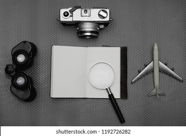 Flat lay of notebook on work desk with retro camera and telescope, Travel concept