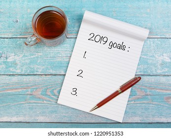 Flat lay with notebook and tea and written the 2019 goals for new year 2019 resolutions