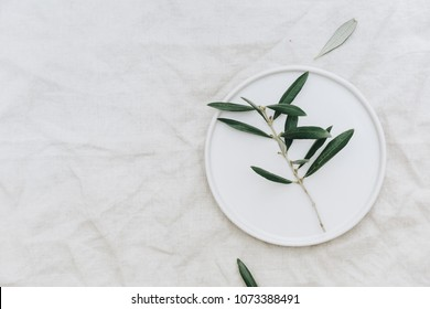 Flat lay olive branch on white plate over linen tablecloth. Organic rustic background with copy space