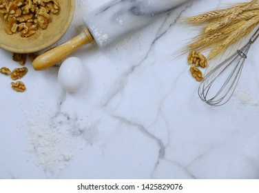 Flat lay on marble table top. Copy space. Food or kitchen themed image of rolling pin, wire wisk, flour, wheat, egg and walnuts