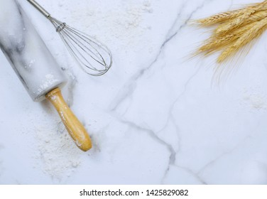Flat lay on marble table top. Copy space. Food or kitchen themed image of rolling pin, wire wisk, flour and wheat. Copy space.