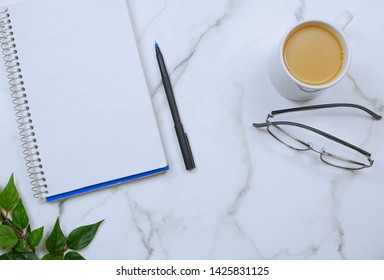 Flat lay on marble table top. Copy space. Items on table are business or school or office oriented and include a spiral notebook, a pen, reading glasses and a cup of coffee.