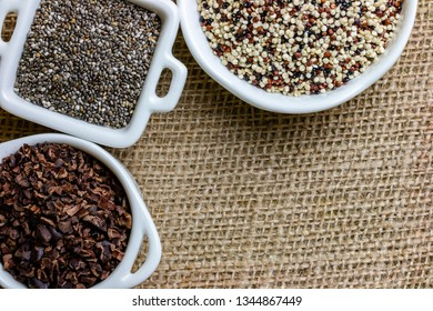 Flat lay on set of superfood like cacao , quinoa and chia seeds : composition space on sack cloth pattern