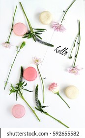 Flat lay on the white background with rose, floowers adn pink macaroons in glam style. Card with text Hello. Top view