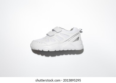 flat lay one white kid running shoes with velcro fasteners on the side with hard shadows in the center isolated on a white background.