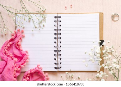 Flat lay: open notebook for records, flowers, a scarf and a wedding ring with pearls. Wedding planning notepad or romantic relationship diary. Concept: dreams of a wedding.
